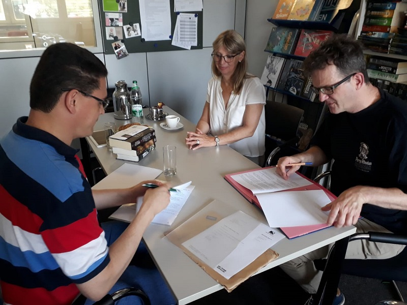 Rodrigo de Lélis (esquerda), Sabine Kropp e Klaus N. Frick (direita) durante a assinatura do contrato para os próximos lançamentos da SSPG.